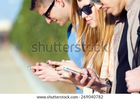 Portrait of a group of students having fun with smartphones after class. - stock photo