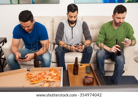 Portrait of a group of three men hanging out but ignoring each other while using their smartphones - stock photo