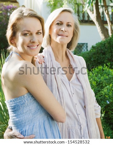 Portrait of a grown up adult daughter and her mature mother enjoying each others company in a home garden and hugging during a sunny day together.