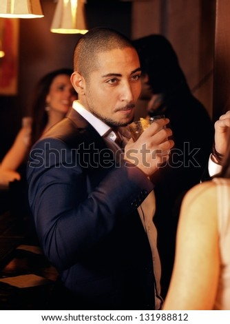 Portrait of a guy at a party holding a glass of whiskey - stock photo