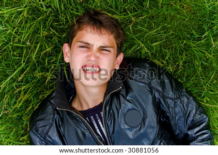 Portrait of a guy lying on the grass - stock photo