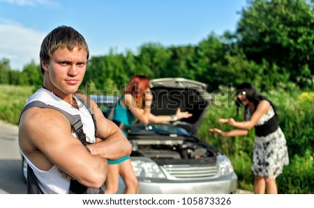 Portrait of a hadsome mechanic with two women on a background - stock photo