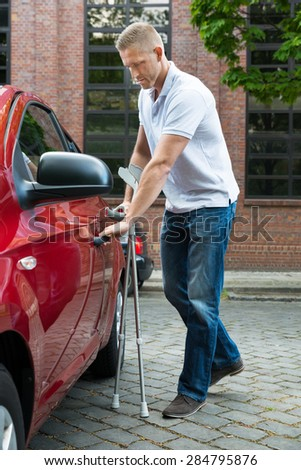 Portrait Of A Handicapped Man With Crutches Opening Door Of A Car - stock photo