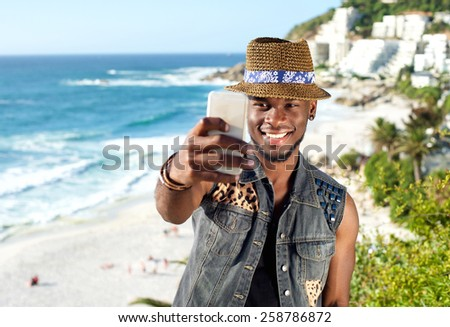 Portrait of a handsome african american man smiling and taking selfie while on vacation at the beach - stock photo