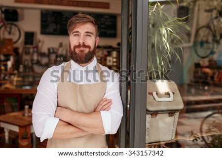 Portrait of a handsome and confident cafe owner standing at the door. Young man standing with his arms crossed looking at camera smiling. - stock photo