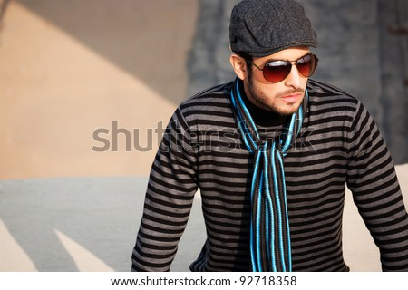 portrait of a handsome and confident man wearing sweater and cap in outdoor, handsome man wearing sunglasses - stock photo