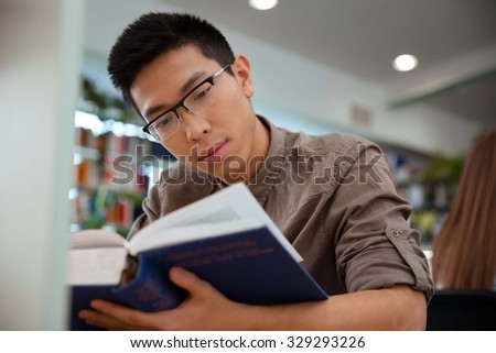 Portrait of a handsome asian male student reading book in university - stock photo