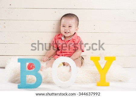 Portrait of a handsome baby boy siting o a floor with BOY wooden letter. baby concept - stock photo