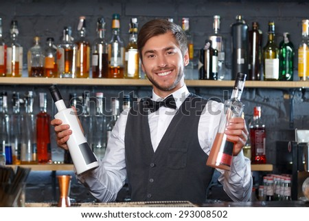 Portrait of a handsome bartender standing at the counter smiling and holding two bottles of liquors , shelves full of bottles with alcohol on the background - stock photo