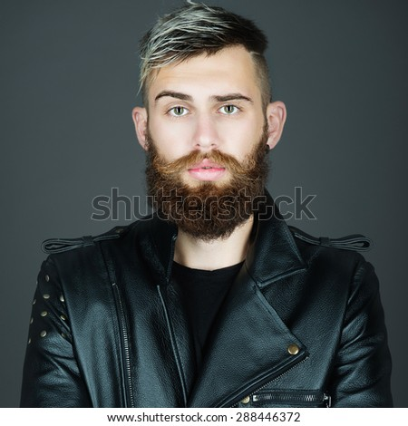 Portrait of a handsome bearded man in a studio in a black leather jacket