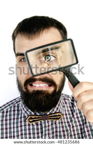 portrait of a handsome bearded man looking through magnifying glass on white background