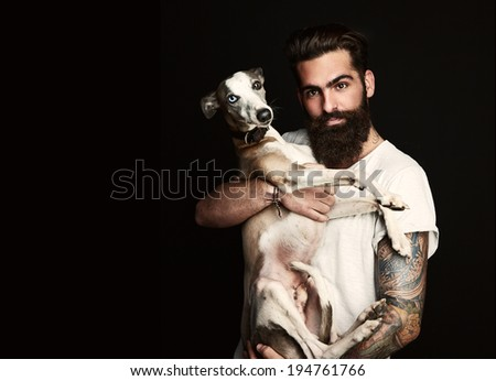 Portrait of a handsome bearded man with his dog - stock photo