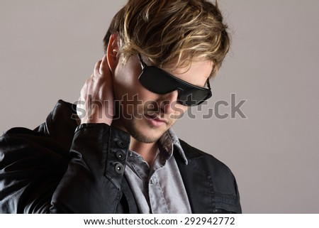 Portrait of a handsome blonde caucasian man wearing a faded blue button shirt, black jacket with leather and sunglasses. - stock photo