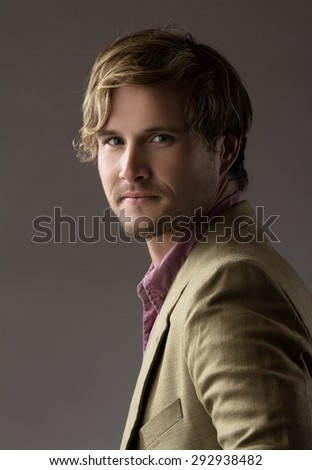 Portrait of a handsome blonde caucasian man wearing a pale purple button shirt with olive beige formal suit jacket. The man is smiling. - stock photo