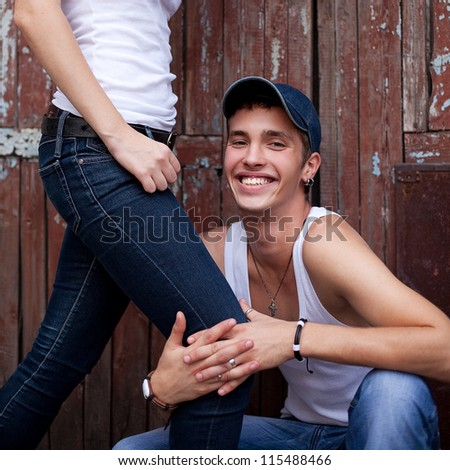 portrait of a handsome boy in jeans sitting next to his standing girlfriend over wooden wall. boy hugging girl's leg. outdoor shot.