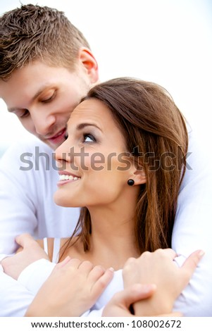 Portrait of a handsome boyfriend hugging his beautiful girlfriend isolated on white - stock photo