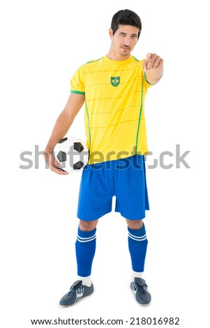 Portrait of a handsome Brazilian football player standing over white background