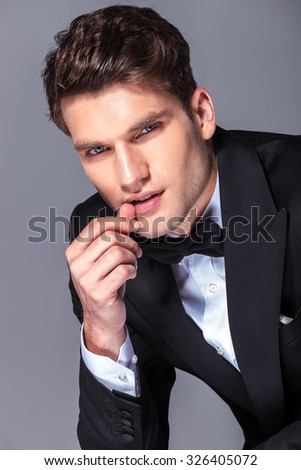 Portrait of a handsome business man holding his thumb near his mouth. - stock photo