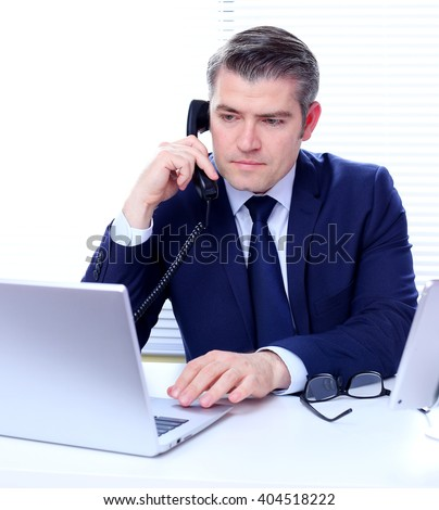 Portrait of a handsome business man talking on a phone in his office.  - stock photo