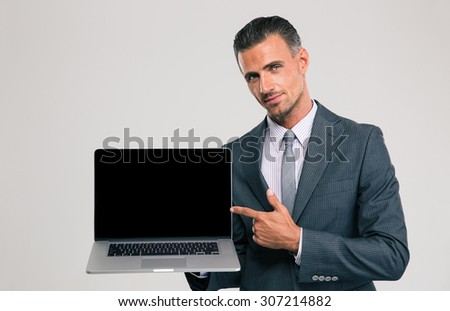 Portrait of a handsome businessman showing blank laptop computer screen isolated on a white background - stock photo
