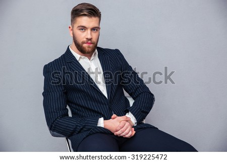 Portrait of a handsome businessman sitting on the office chair over gray background - stock photo