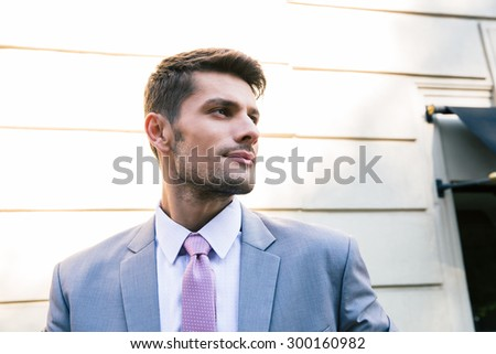 Portrait of a handsome businessman standing outdoors and looking away - stock photo