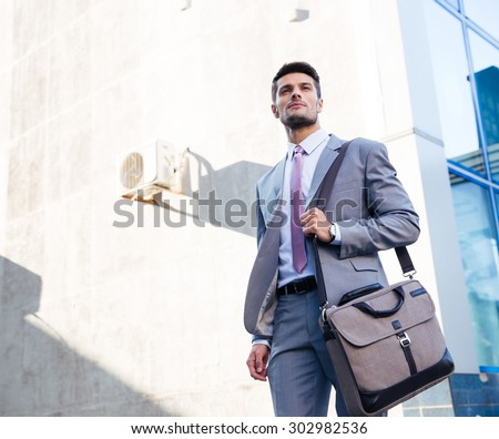 Portrait of a handsome businessman standing outdoors near office building - stock photo