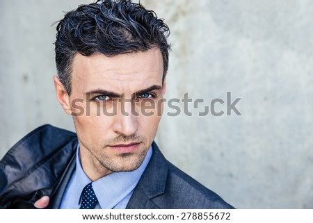 Portrait of a handsome businessman standing over concrete wall and looking at camera - stock photo