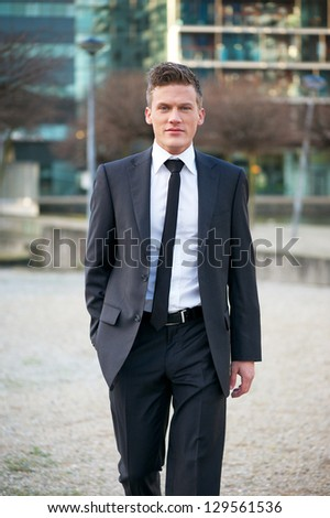 Portrait of a handsome businessman walking in the city - stock photo