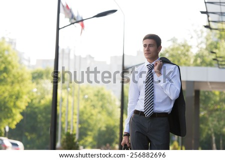 Portrait of a handsome businessman walking on the street near office building