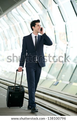 Portrait of a handsome businessman walking on train station platform and talking on the phone - stock photo