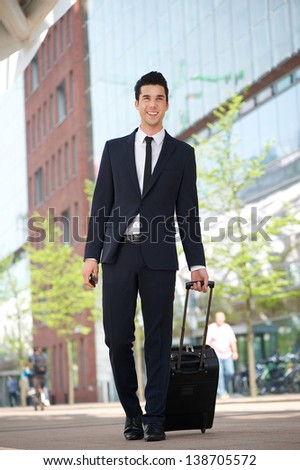 Portrait of a handsome businessman walking outdoors with bag - stock photo