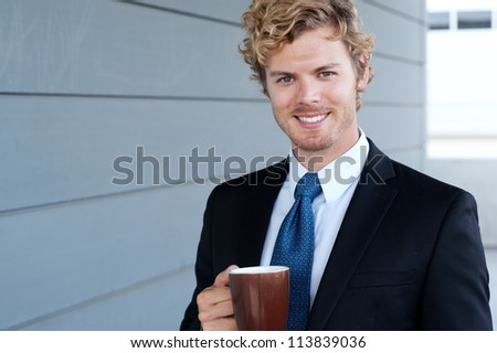 portrait of a handsome businessman with coffee mug - stock photo