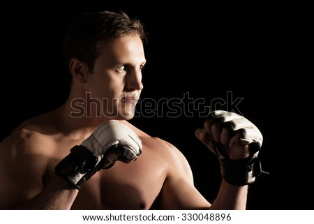 Portrait of a handsome caucasian male mixed martial arts fighter. The guy is wearing white mma gloves. - stock photo