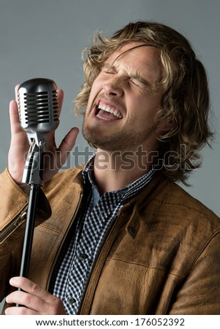 Portrait of a handsome caucasian male singer wearing a blue checkered button shirt and a leather jacket. The man is singing into a silver performance microphone. - stock photo