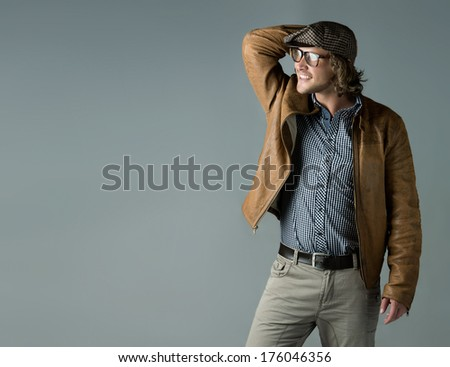 Portrait of a handsome caucasian man wearing a leather jacket blue checkered button shirt beret and retro glasses. - stock photo