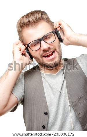 Portrait of a handsome caucasian young man with glasses singing and listening to music in headphones isolated on white background. - stock photo
