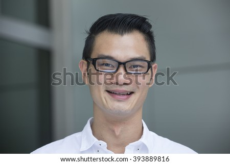 Portrait of a handsome Chinese man smiling and looking at the camera. - stock photo