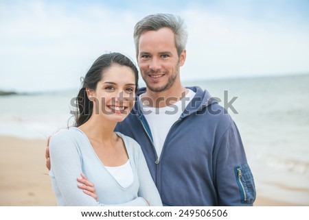 Portrait of a handsome couple at the beach in casual clothes looking at the camera - stock photo