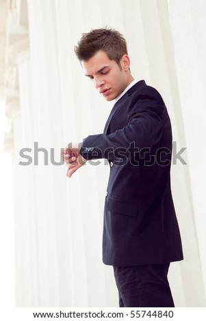 portrait of a handsome elegant young man checking his watch - stock photo