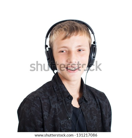 Portrait of a handsome European teen boy wearing a black shirt with headphones. Smiling face. Studio shot, isolated on white background.