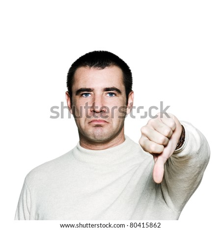 Portrait of a handsome expressive man showing thumbs down sign in studio on white isolated background - stock photo
