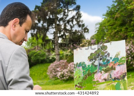 Portrait of a handsome fashionable male artist working outdoors in the park or garden on a trestle and easel painting with oils and acrylics during an art class - stock photo