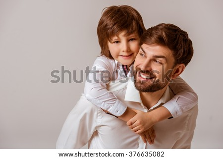 Portrait of a handsome father carrying his cute son on back and smiling. Both in white classical shirts standing on a gray background.