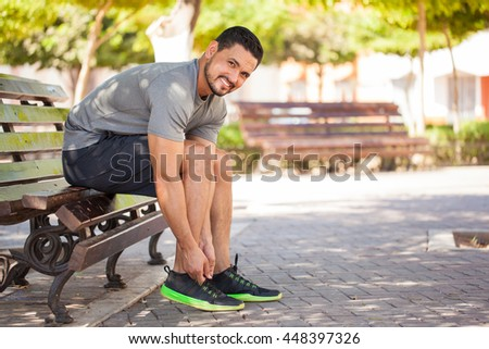 Portrait of a handsome Hispanic young man getting ready to go running at a park and smiling - stock photo