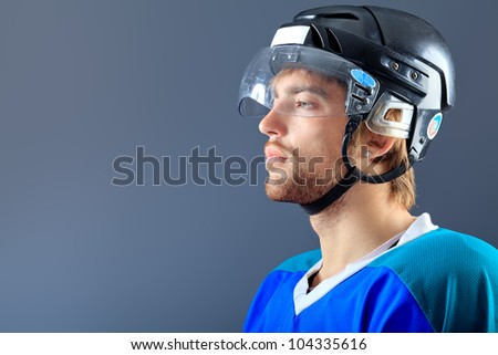 Portrait of a handsome ice-hockey player. Studio shot. - stock photo