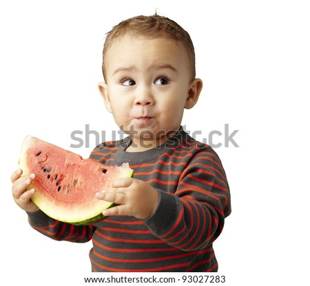 portrait of a handsome kid holding a watermelon and tasting over white - stock photo