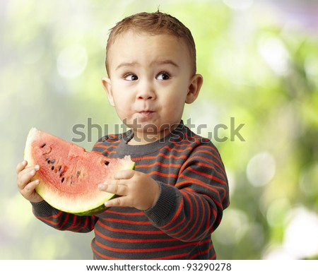 portrait of a handsome kid holding a watermelon slice - stock photo
