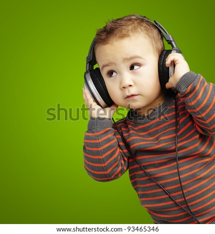 portrait of a handsome kid listening to music looking up against a green background - stock photo