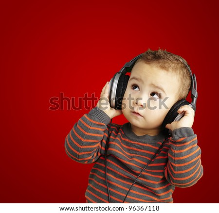 portrait of a handsome kid listening to music looking up over re